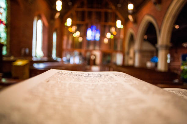 Close up of open bible on altar of Anglican church Color image depicting a close up wide angle view of the pages of an open bible on the altar of an Anglican church. Focus is on the bible in the foreground, while the background consists of the defocused interior of the church. Wooden pews recede into the distance and the lights illuminating the church appear as out of focus balls of light. The church has a warm, welcoming orange glow. Lots of room for copy space. pulpit stock pictures, royalty-free photos & images