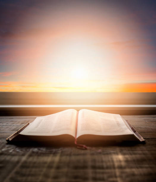 Close up of open Bible, with dramatic light. Wood table with sun rays coming through window. Christian image stock photo