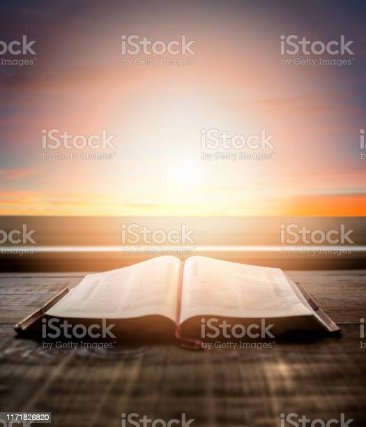 Photo of Close up of open Bible, with dramatic light. Wood table with sun rays coming through window. Christian image