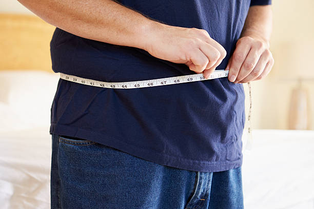 Close Up Of Overweight Man Measuring Waist stock photo