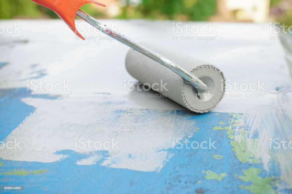 Close up of paint roller painting a metal surface stock photo