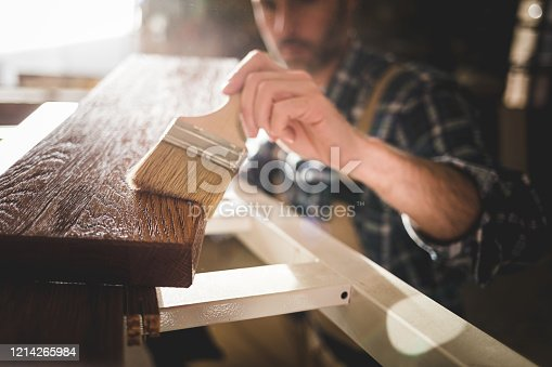 Close up of paintbrush applies paint or varnish on wooden board in carpentry workshop
