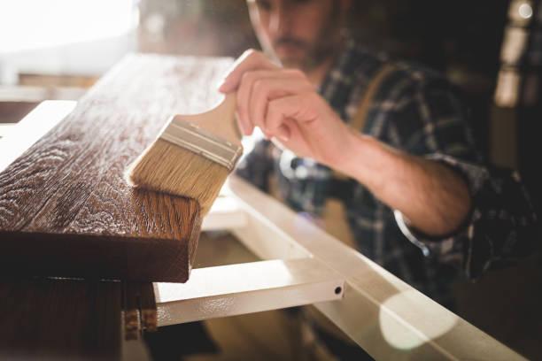sluit omhoog van penseel past verf of vernis op houten raad in timmerwerkplaats toe - houtbeits stockfoto's en -beelden