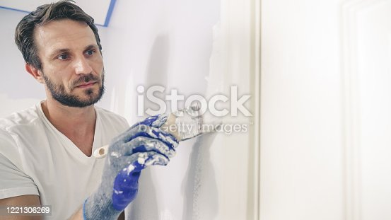 istock Close up of painter hands with gloves painting the wall edge by door frame. 1221306269