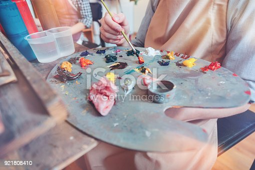624112404istockphoto Close up of painter mixing shades on palette 921808410