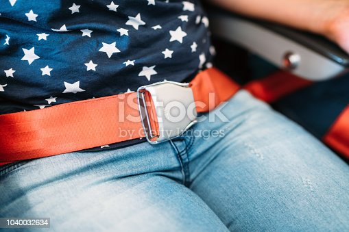 istock Close up of passenger hands fasten belts while sitting on airplane seat 1040032634