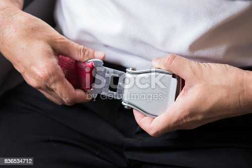 istock Close up of passenger hands fasten belts while sitting on airplane seat. 836534712