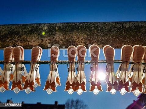 Close up of pegs for clothes on a line in front of the clear blue sky during sunshine