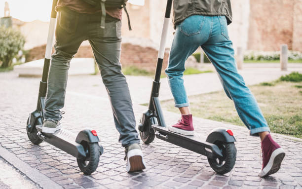 Close up of people couple using electric scooter in city park - Millenial students riding new modern ecological mean of transport - Green eco energy concept with zero emission - Warm sunshine filter stock photo