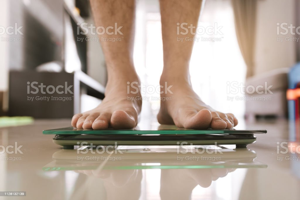 Close up of people feet standing on scale weighing. stock photo
