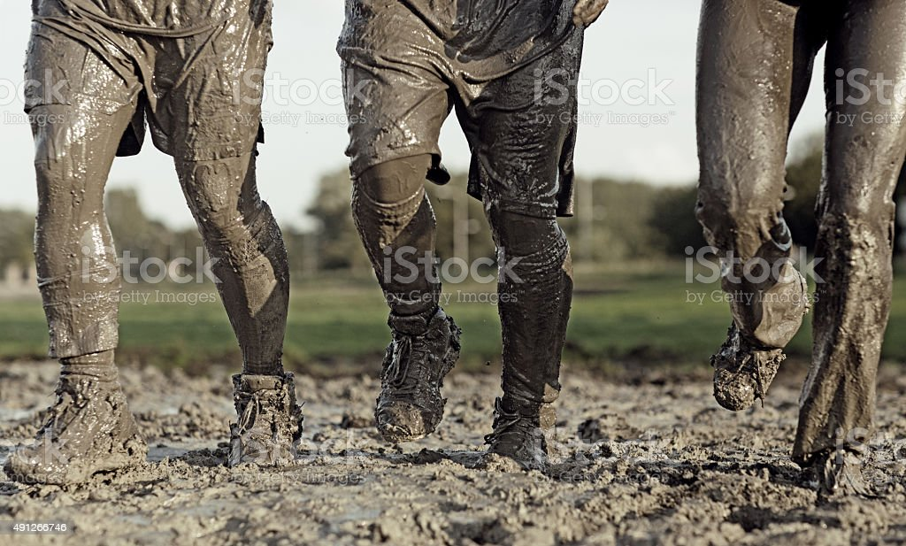 close up of people jogging in mud stock photo