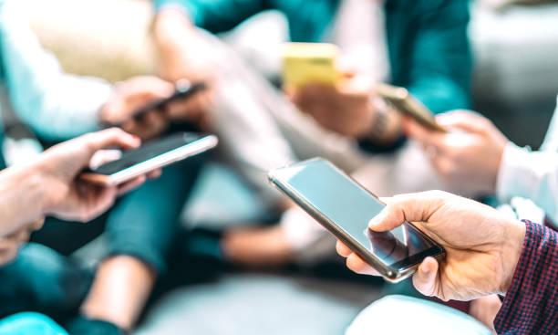 primo piano delle persone che usano gli smartphone mobili - dettaglio degli amici che condividono foto sul social network con smartphone - concetto tecnologico e cultura del cellulare con focus selettivo sulla mano destra - assuefazione foto e immagini stock
