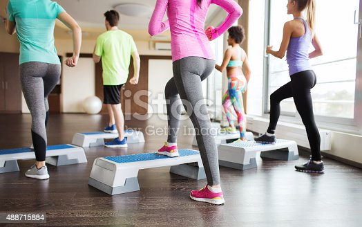 istock close up of people working out with steppers in gym 488715884