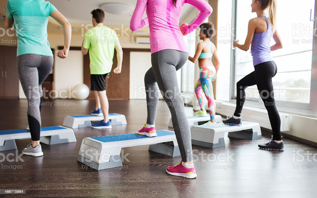 close up of people working out with steppers in gym stock photo