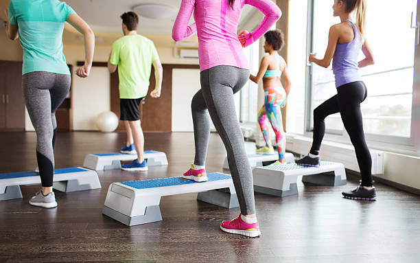 close up of people working out with steppers in gym - aerobics stock photos and pictures