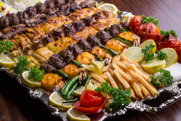 Close up of Persian Mix Kebab consisting of minced meat, chicken and steak with french fries (chips) on a large tray Close up of Persian Mix Kebab consisting of minced meat, chicken and steak with french fries (chips) on a large tray persian culture stock pictures, royalty-free photos & images
