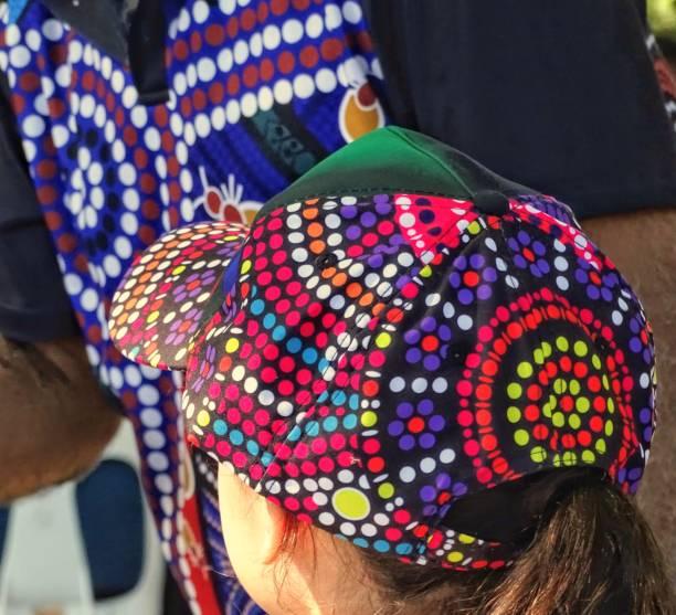 close up of person wearing an Australian Aboriginal tribal design cap at Aboriginal festival stock photo