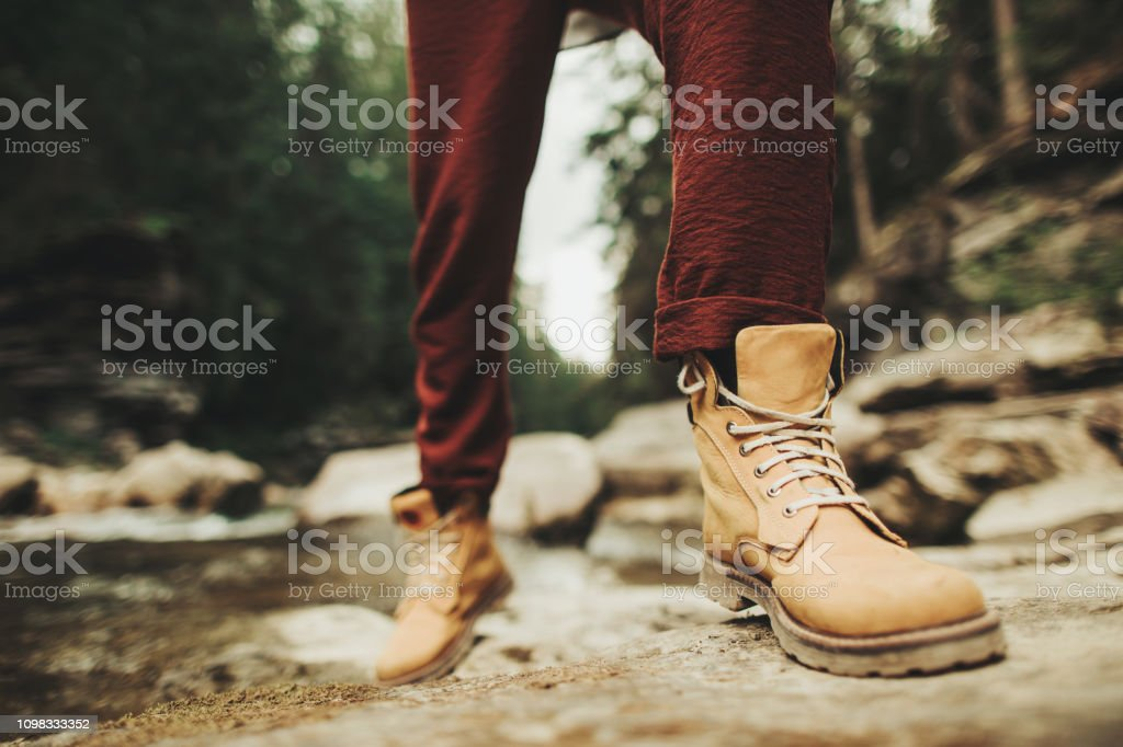 Close Up Of Persons Boots On The Bank Of Mountaint River