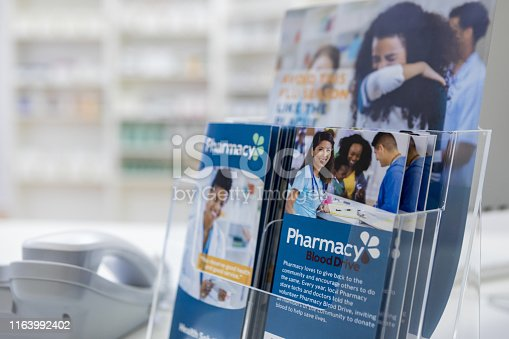 Informational brochures and flyers sit on a pharmacy counter. The brochures and flyers detail the pharmacy's services.