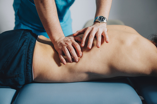 Physical therapist is using his hands to massage the lower back of a male patient lying on his stomach.