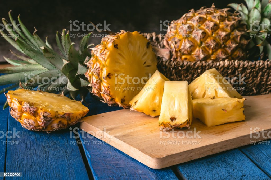 Close up of Pineapple fruit with slices on blue wooden table royalty-free stock photo