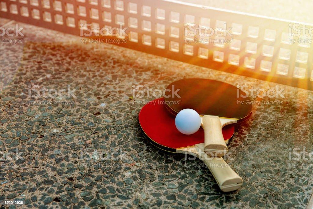 d8199b3be perto da bola de pingue-pongue com raquetes de tênis na pedra ténis de mesa