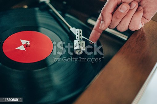 Turntable vinyl record player with vinyl records  on a wooden table.
