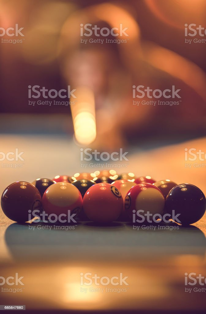 Close up of pool balls on the table with person in the background. stock photo