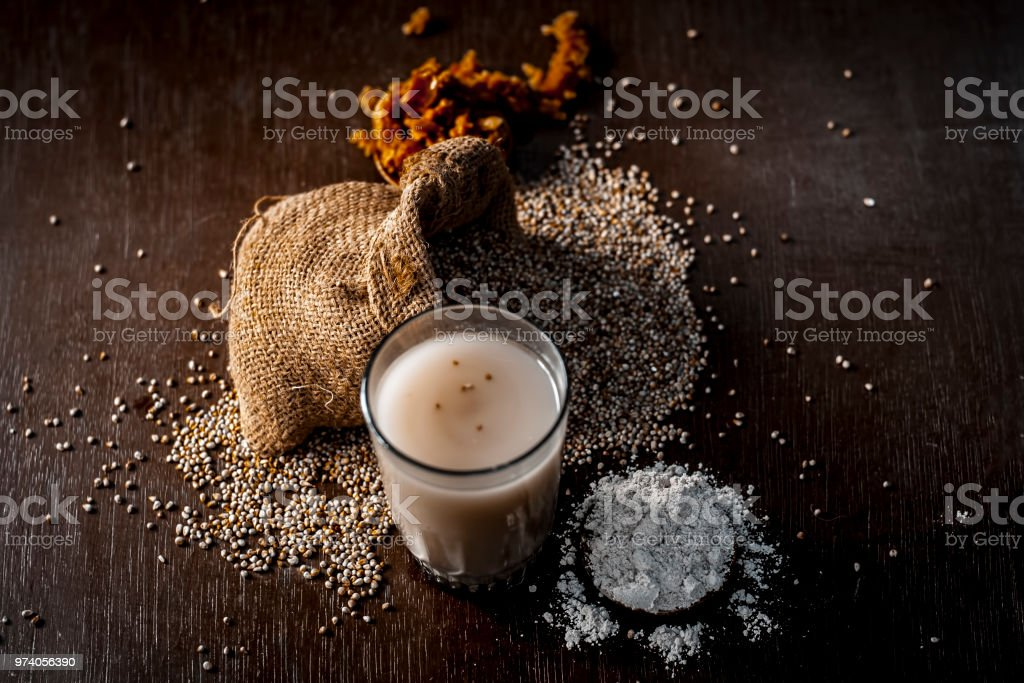 Close up of popular summer drink i.e. Barley kanji in glass with all its ingredients on a wooden surface isolated on a white surface.; stock photo