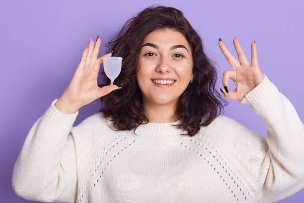 close up of portrait of young woman holding silicon menstrual cup isolated over lilac background in studio, showing ok sign, feelsgood during her period. modern eco friendly female hygiene concept. - coppa mestruale foto e immagini stock