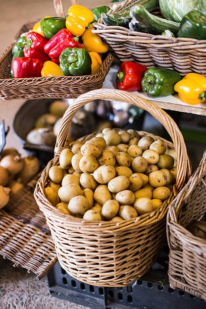 Close up of potatoes in a basket surrounded by peppers. stock photo