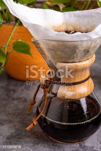 Bright, vibrant picture of drip coffee with a dark grey counter top and a green plant behind the coffee pot