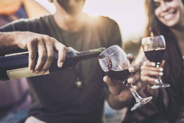Close up of pouring red wine into a glass outdoors. Close up of a couple drinking wine outdoors while man is pouring it into a glass. pouring stock pictures, royalty-free photos & images