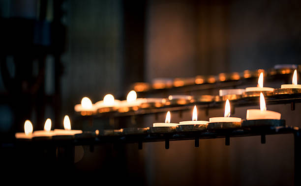 close up of prayer candles in a row in church - catholicism stock photos and pictures