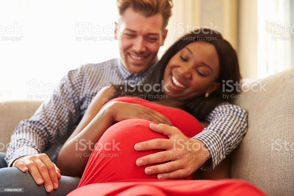 Close Up Of Pregnant Couple At Home Relaxing On Sofa stock photo