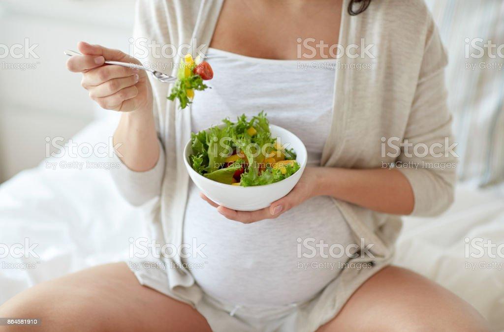 Nahaufnahme von Schwangeren zu Hause essen Salat – Foto