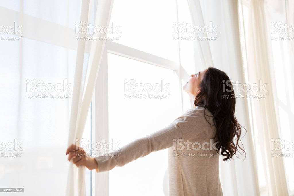 close up of pregnant woman opening window curtains stock photo