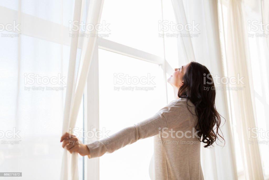 Nahaufnahme von schwangeren öffnen Fenstervorhänge – Foto