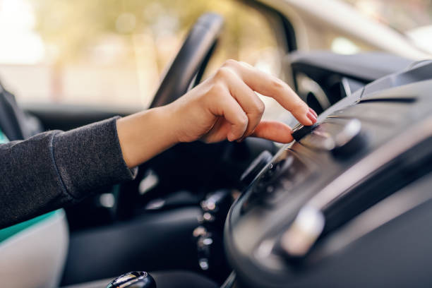 close up of pregnant woman searching radio station while sitting in car. other hand on steering wheel. - radio foto e immagini stock