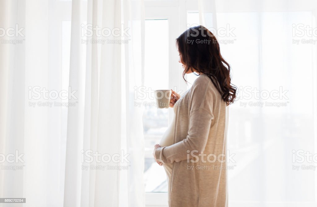 close up of pregnant woman with tea cup at window stock photo