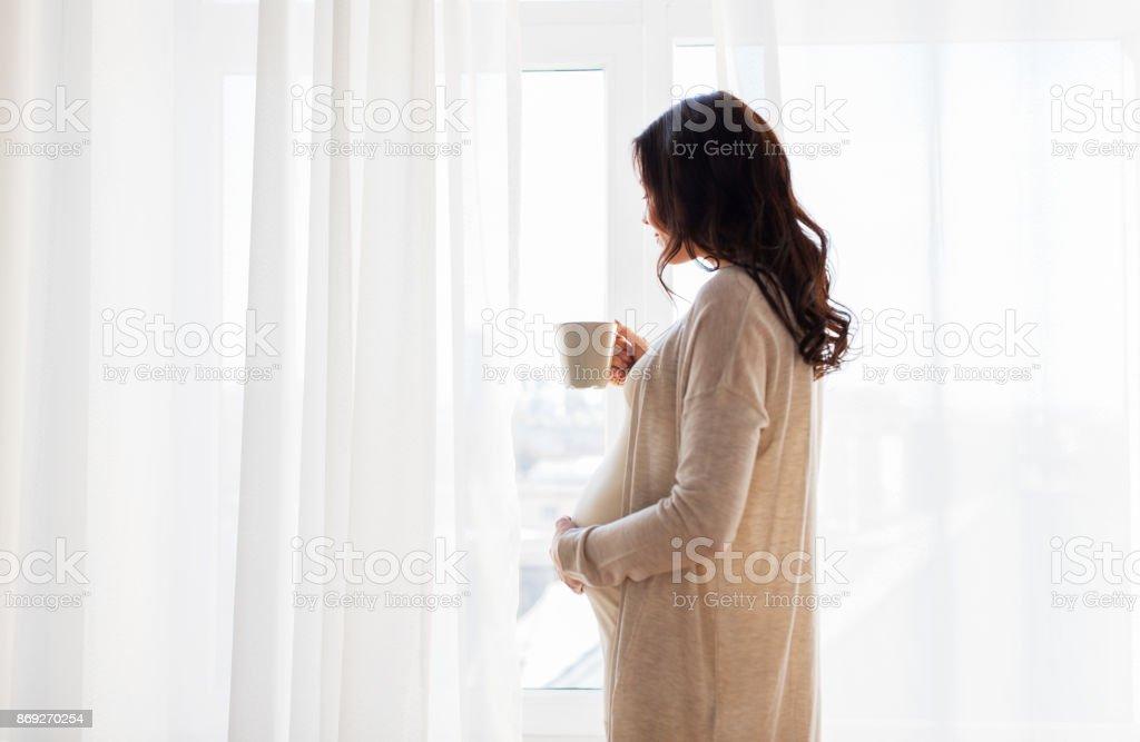 Nahaufnahme von Schwangeren mit Teetasse am Fenster – Foto