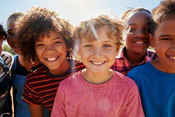 Close up of pre-teen friends in a park smiling to camera Close up of pre-teen friends in a park smiling to camera children only stock pictures, royalty-free photos & images
