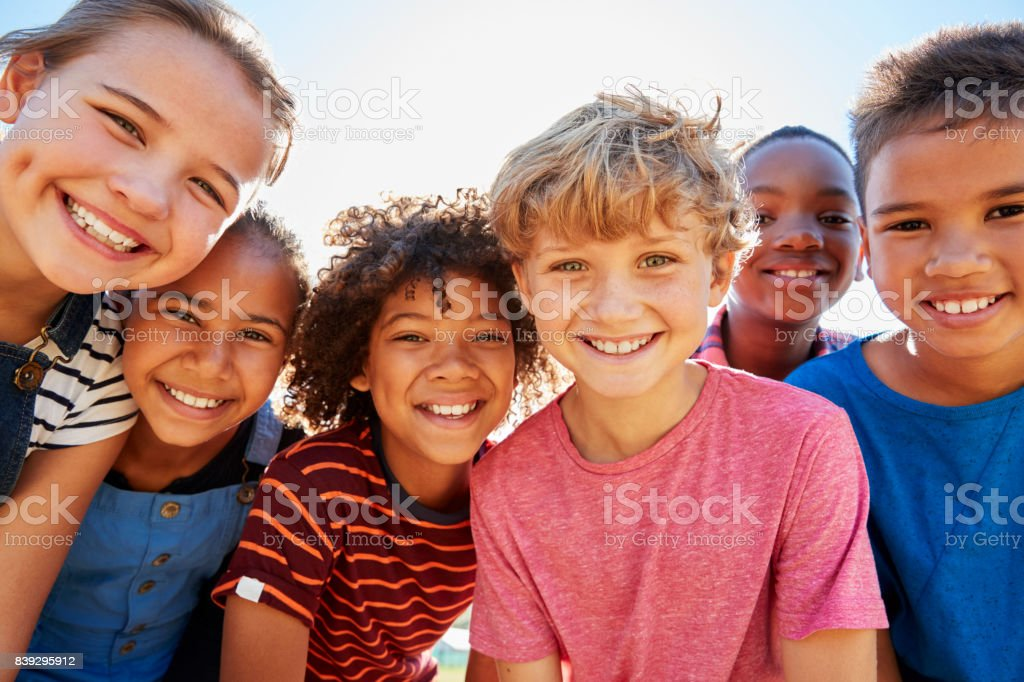 Close up of pre-teen friends in a park smiling to camera - foto stock
