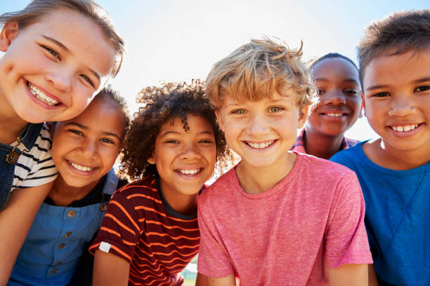 close up of pre-teen friends in a park smiling to camera - child stock photos and pictures