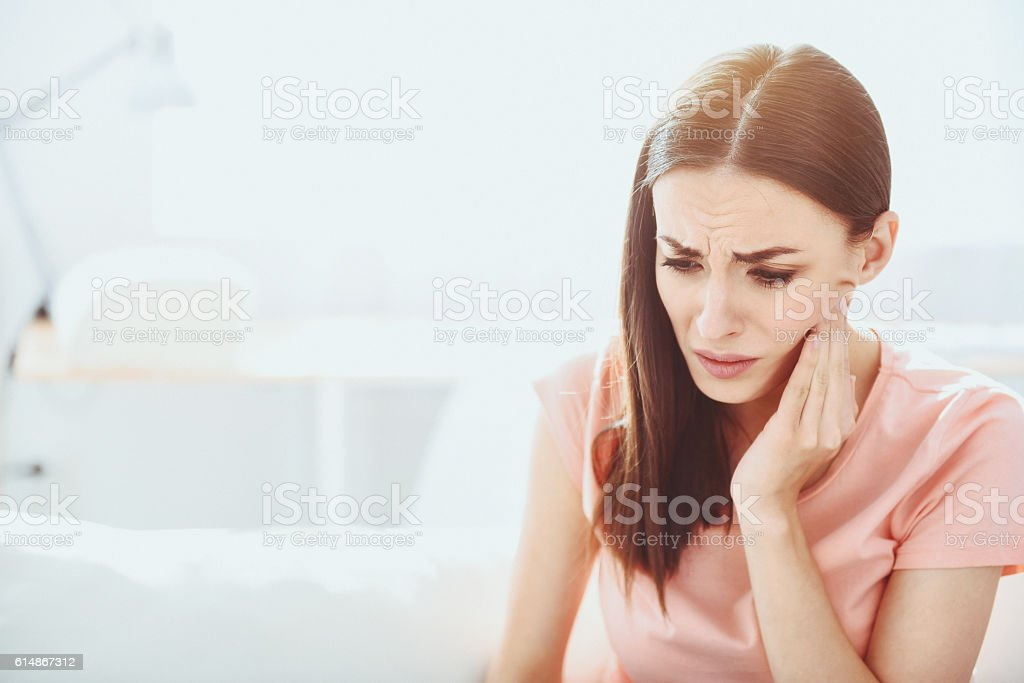 Close up of pretty disappointed woman which having toothache. stock photo