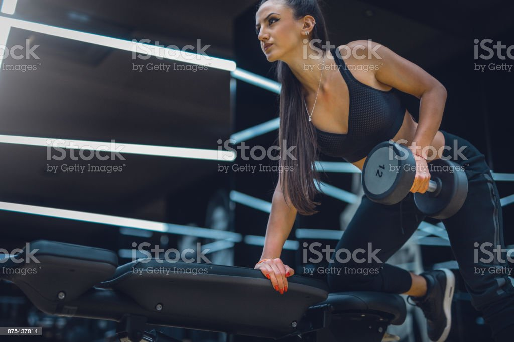 Close up of pretty female doing workout in gym stock photo
