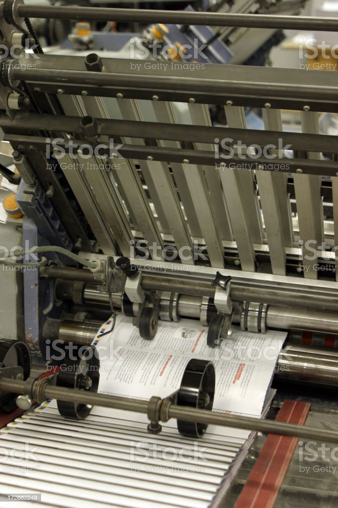 Close up of printing press producing brochures stock photo