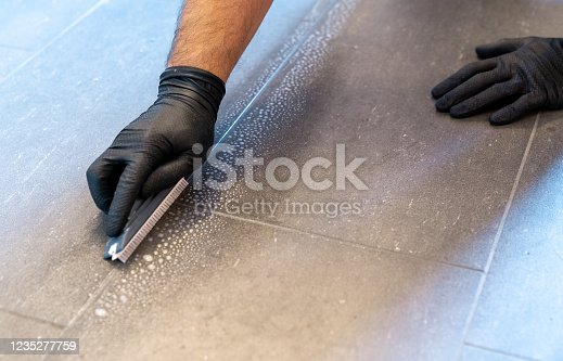 A close up of a professional cleaner cleaning grout with a brush blade and foamy soap on a gray tiled bathroom floor