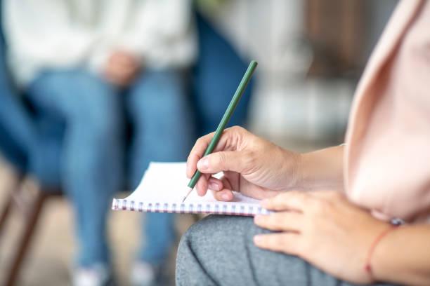 Nahaufnahme des Psychologen, der stiften, während er Notizen macht – Foto