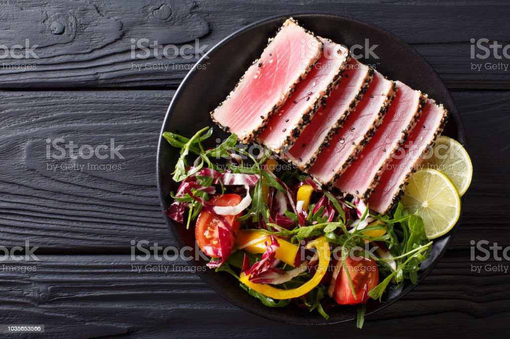 Close up of rare seared Ahi tuna slices with fresh vegetable salad. Top view horizontal stock photo